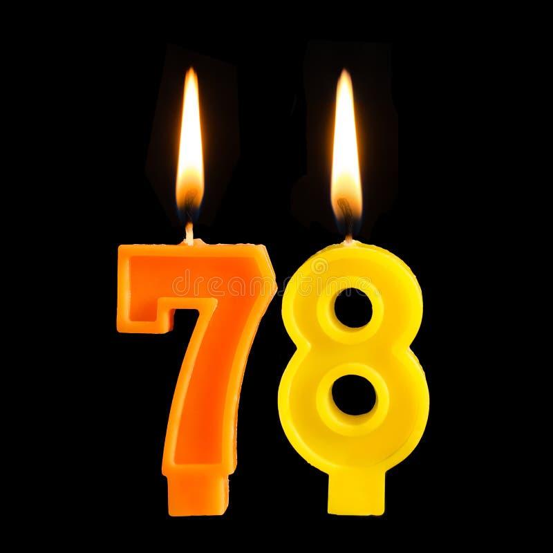 Bougies brûlantes d'anniversaire sous forme de 78 soixante-dix-huit pour le gâteau d'isolement sur le fond noir photos stock