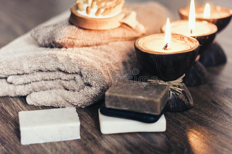 Bougies brûlantes d'arome de station thermale dans la coquille de noix de coco, le savon fait main, la serviette et le gant de to image stock