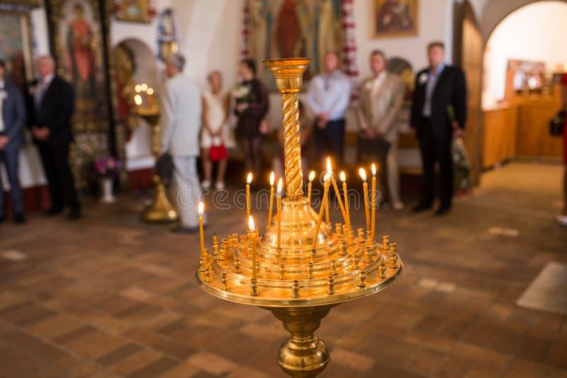 Bougies brûlantes de cire dans un chandelier dans l'église photographie stock libre de droits