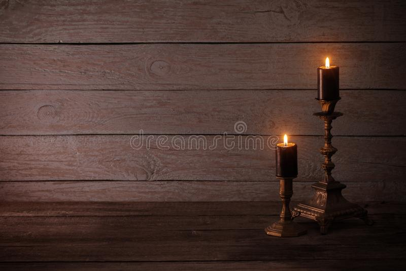 Bougies brûlantes noires dans des chandeliers sur le vieux fond en bois image stock