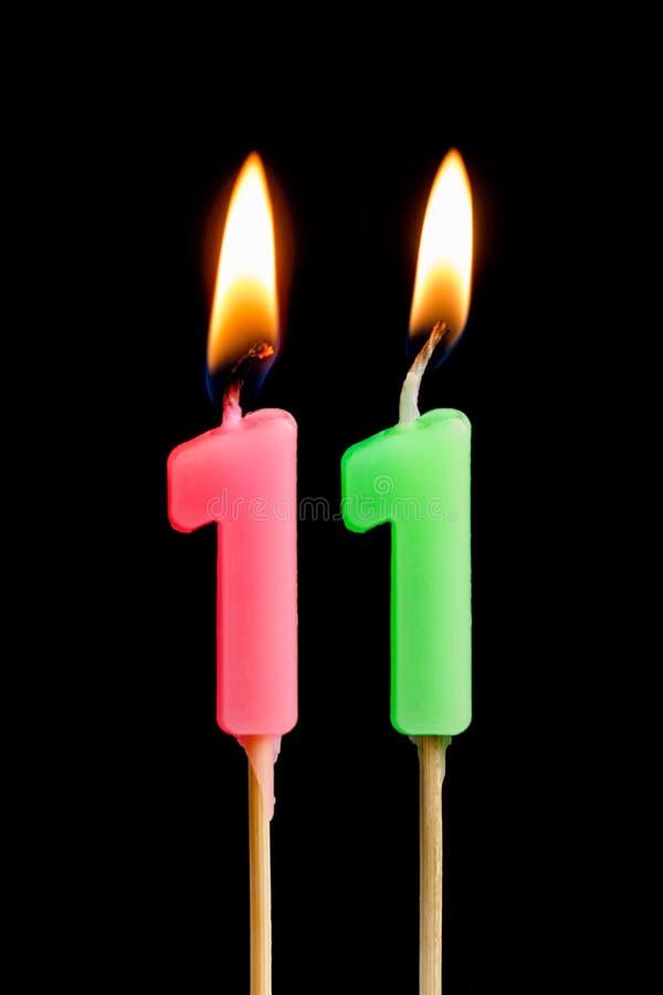 Bougies brûlantes sous forme de 11 onze figures nombres, dates pour le gâteau d'isolement sur le fond noir Le concept du celebrat images stock