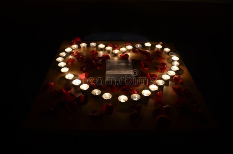 Bougies brûlantes sous la forme de coeur entourée par les pétales de rose rouges dans t photos stock
