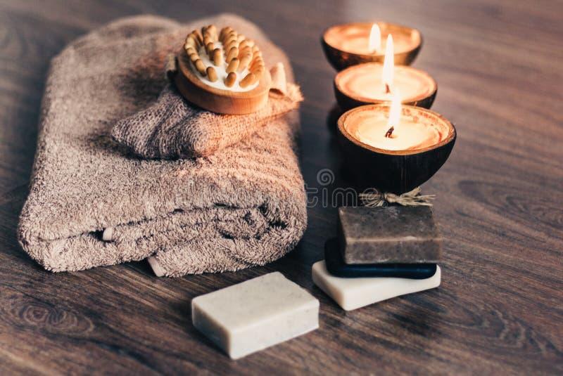 Bougies br?lantes d'arome de station thermale dans la coquille de noix de coco, le savon fait main, la serviette et le gant de to photos libres de droits