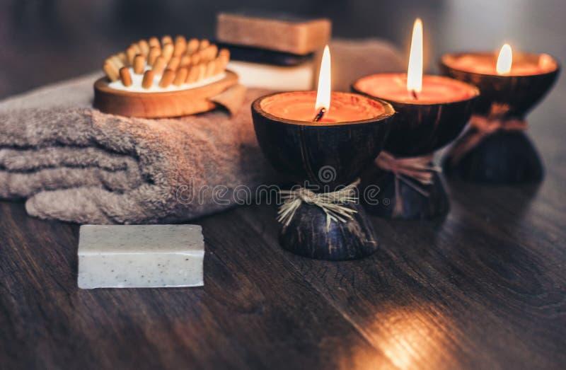Bougies br?lantes d'arome de station thermale dans la coquille de noix de coco, le savon fait main, la serviette et le gant de to photo stock