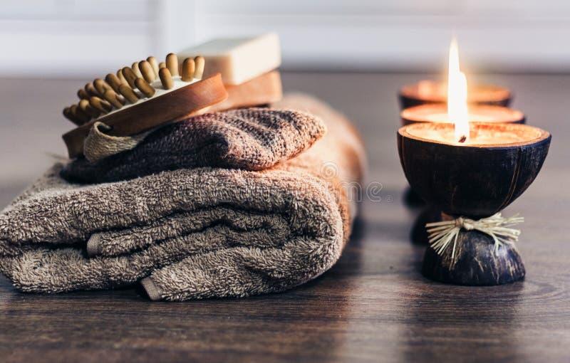 Bougies br?lantes d'arome de station thermale dans la coquille de noix de coco, le savon fait main, la serviette et le gant de to images stock