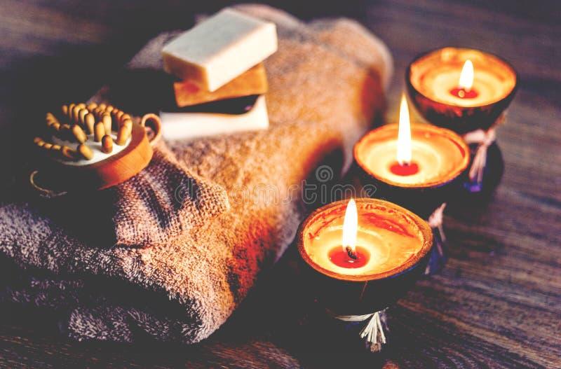 Bougies br?lantes d'arome de station thermale dans la coquille de noix de coco, le savon fait main, la serviette et le gant de to image libre de droits