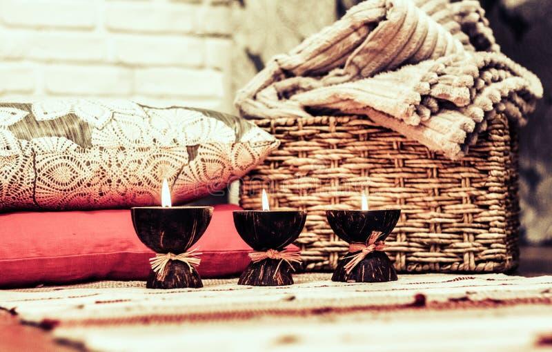 Bougies br?lantes d'arome de station thermale dans la coquille de noix de coco, les oreillers et le plaid, fond int?rieur ? la ma photo stock