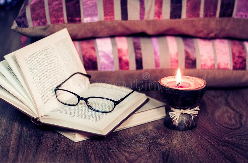 Bougies br?lantes d'arome de station thermale dans la coquille de noix de coco, les oreillers, les verres et les livres, fond int photos libres de droits