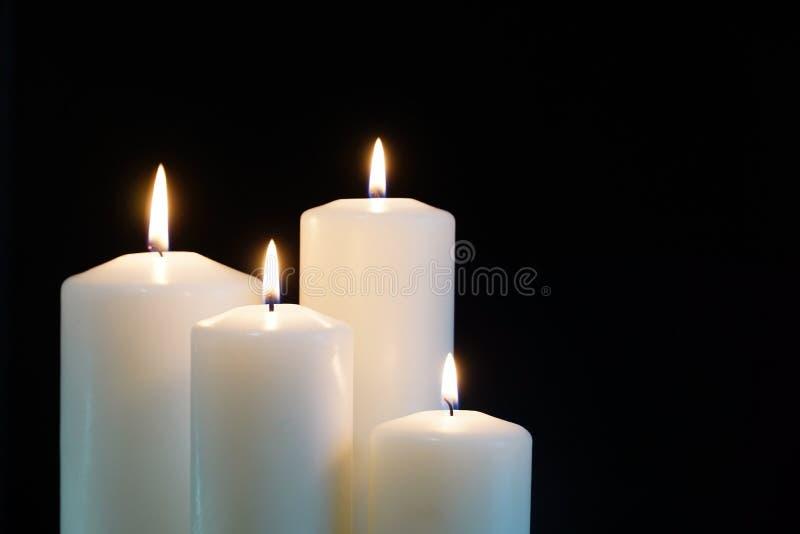 Bougies brûlantes d'isolement sur le fond noir images stock