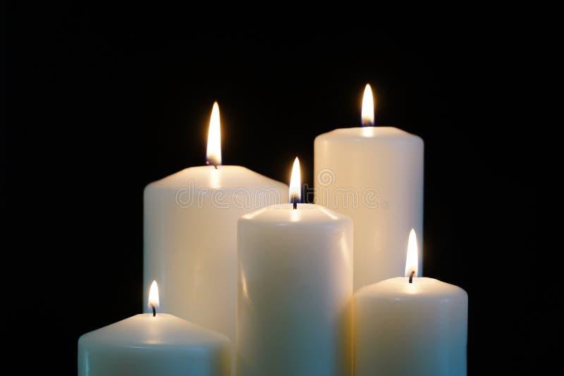 Bougies brûlantes d'isolement sur le fond noir image libre de droits