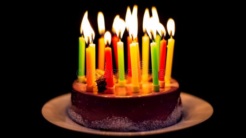 Bougies colorées brûlant sur le gâteau de chocolat appétissant, célébration de partie, douce photos stock