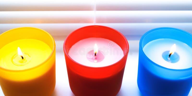 Bougies colorées lumineuses Bougies colorées parfumées avec les mèches allumées image libre de droits