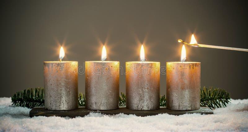 Bougies d'avènements de la lumière quatre avec des matchs photographie stock