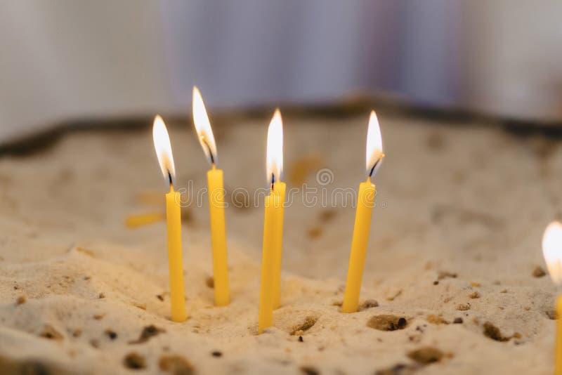 Bougies dans l'église dans le sable photographie stock libre de droits