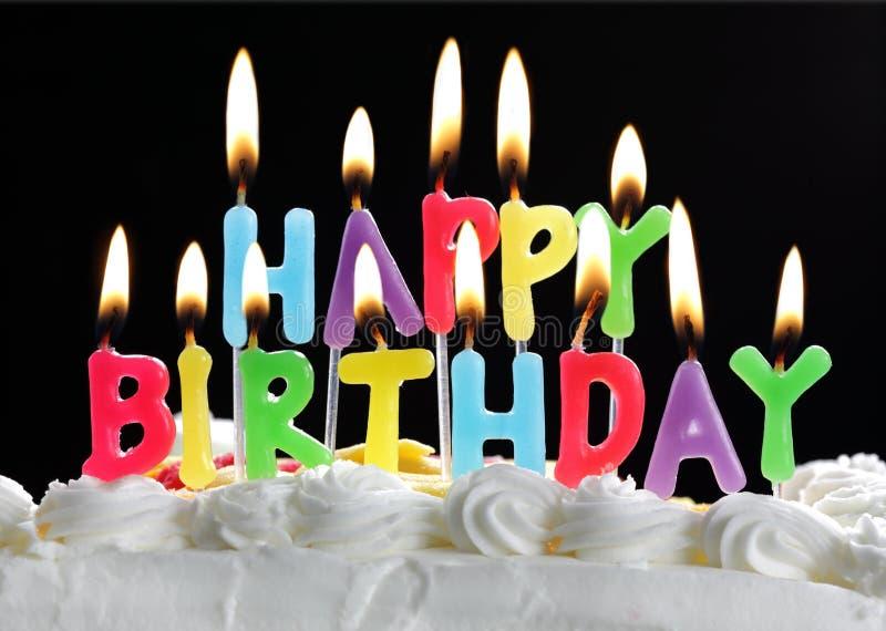 Bougies de joyeux anniversaire sur un gâteau photographie stock libre de droits