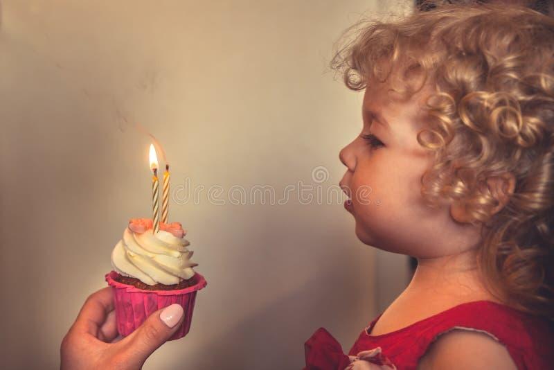 Bougies de soufflement d'enfant mignon sur le gâteau d'anniversaire image libre de droits