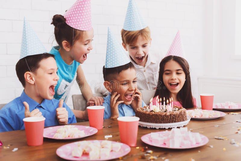 Bougies de soufflement de garçon sur le gâteau d'anniversaire, célébrant avec des amis photo libre de droits