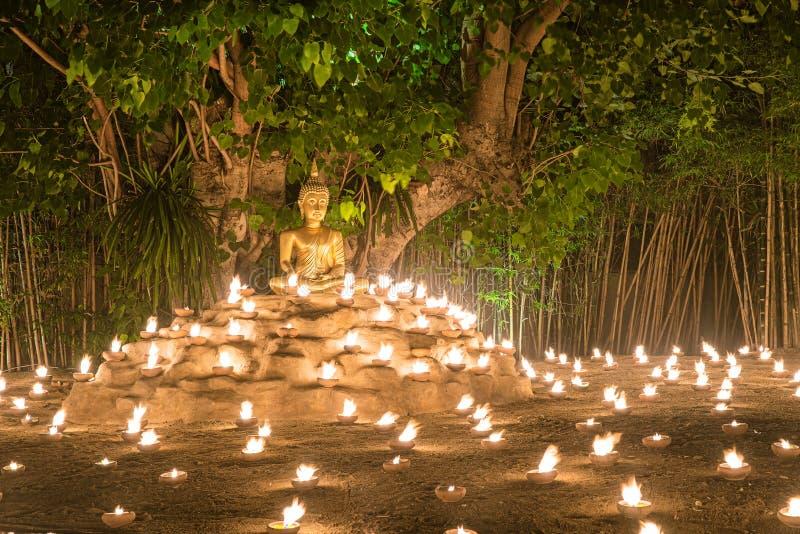 Bougies du feu de moine bouddhiste au Bouddha avec la belle réflexion de l'eau en Phan Tao Temple, Chiangmai, Thaïlande photographie stock libre de droits