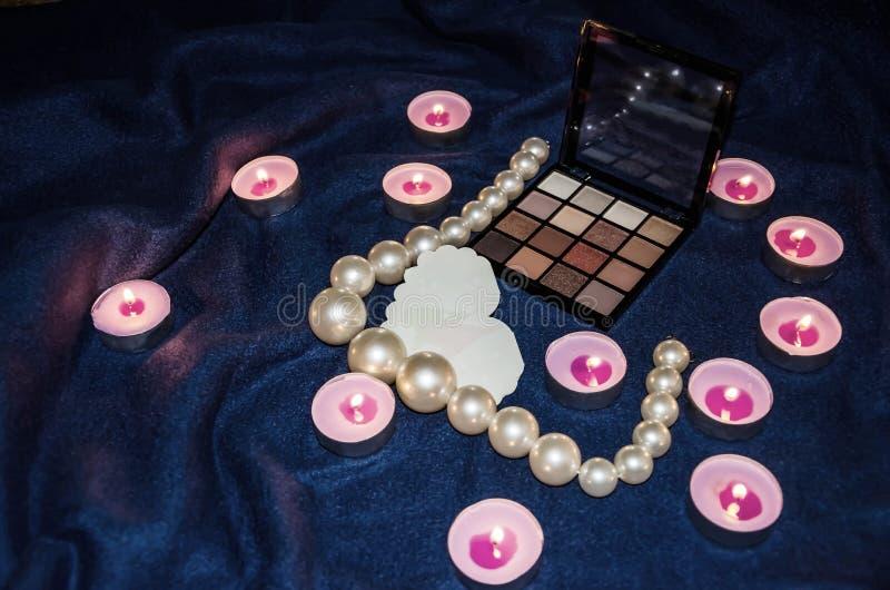 Bougies flairées, une palette des ombres, un coeur et belles perles sur une couverture images stock