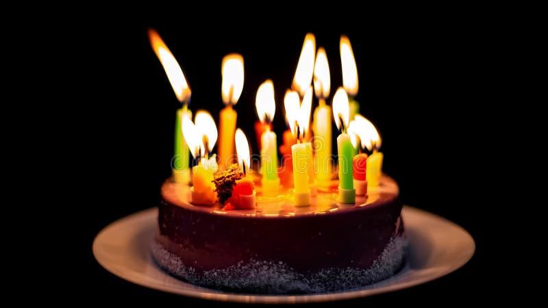 Bougies grillant sur le gâteau de chocolat délicieux, d'isolement sur le fond noir photos stock