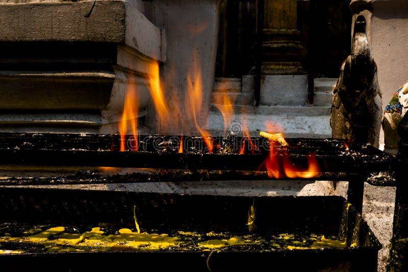 Bougies jaunes brûlant sur le support noir en métal avec la flamme orange et les larmes jaunes de bougie dessous dans un temple b photos stock