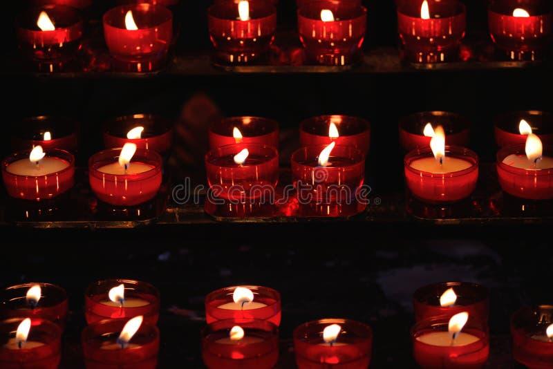 Bougies rouges brûlantes dans une église image stock