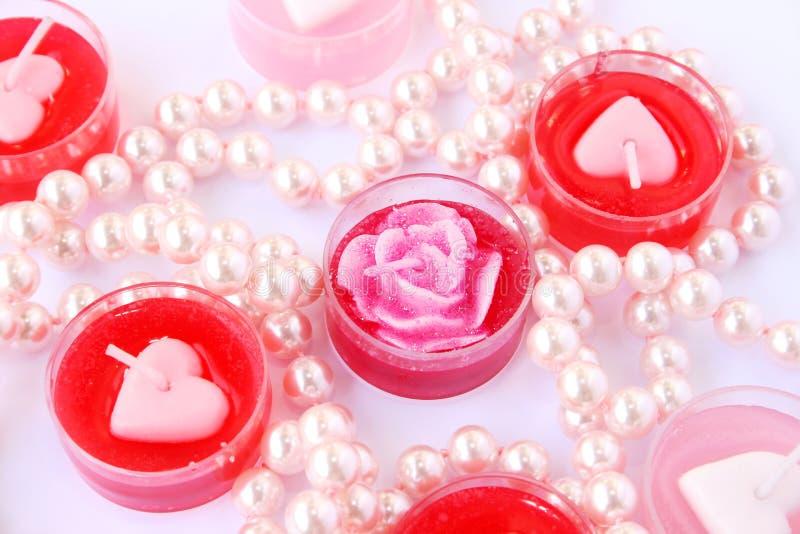 Bougies rouges et roses avec le collier photographie stock libre de droits
