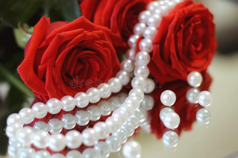Bouguet of red roses with green leaves, with a necklace of white pearls and scattered beads reflected in the mirror closeup. stock photo