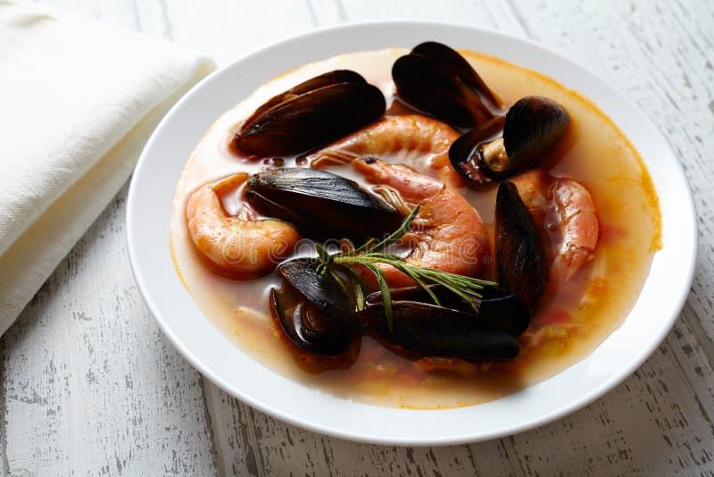 Bouillabaisse della minestra dei frutti di mare del pesce Cozze, gamberetto, aragosta in salsa al pomodoro Priorità bassa di legn fotografia stock