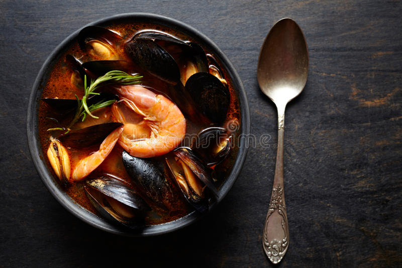 Bouillabaisse soup. Fish stew with mussels, shrimp, tomato and lobster. Traditional dish in France. Dark rustic style. royalty free stock photo