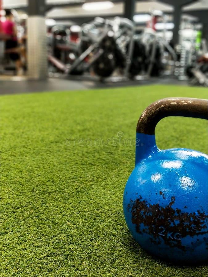 Bouilloire-cloche bleue sans marque sur l'herbe artificielle dans un gymnase photos stock