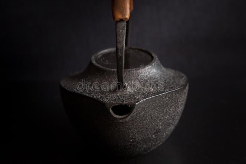 Bouilloire de thé asiatique moderne de style sur le fond noir photographie stock libre de droits