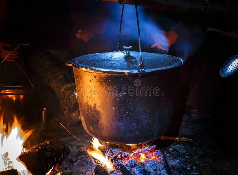 Bouilloire de touristes fumée au-dessus du feu de camp le soir Montagnes de ressort photo stock