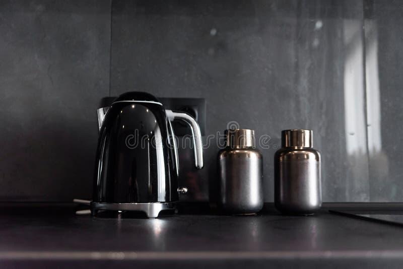 Bouilloire et bouteilles noires modernes pour des épices se tenant sur l'espace de travail noir de cuisine sur le fond de la tuil photos libres de droits