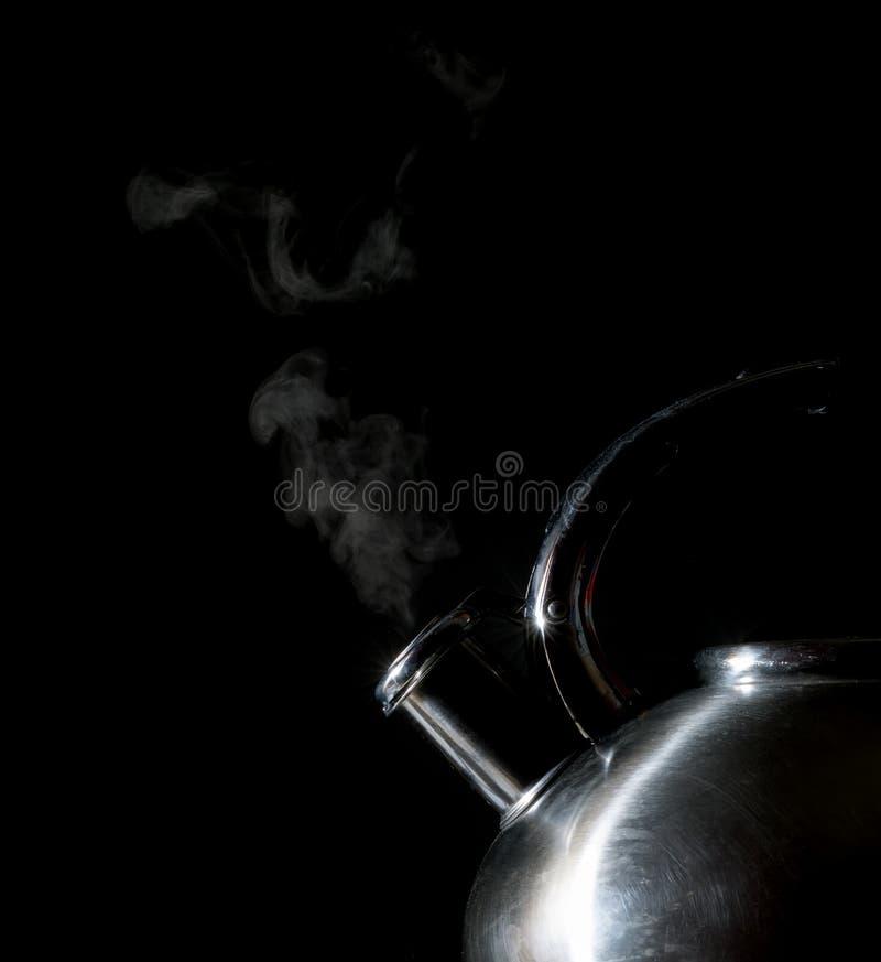Bouilloire sifflant, bouilloire de ébullition, vapeur, sur un noir photos stock