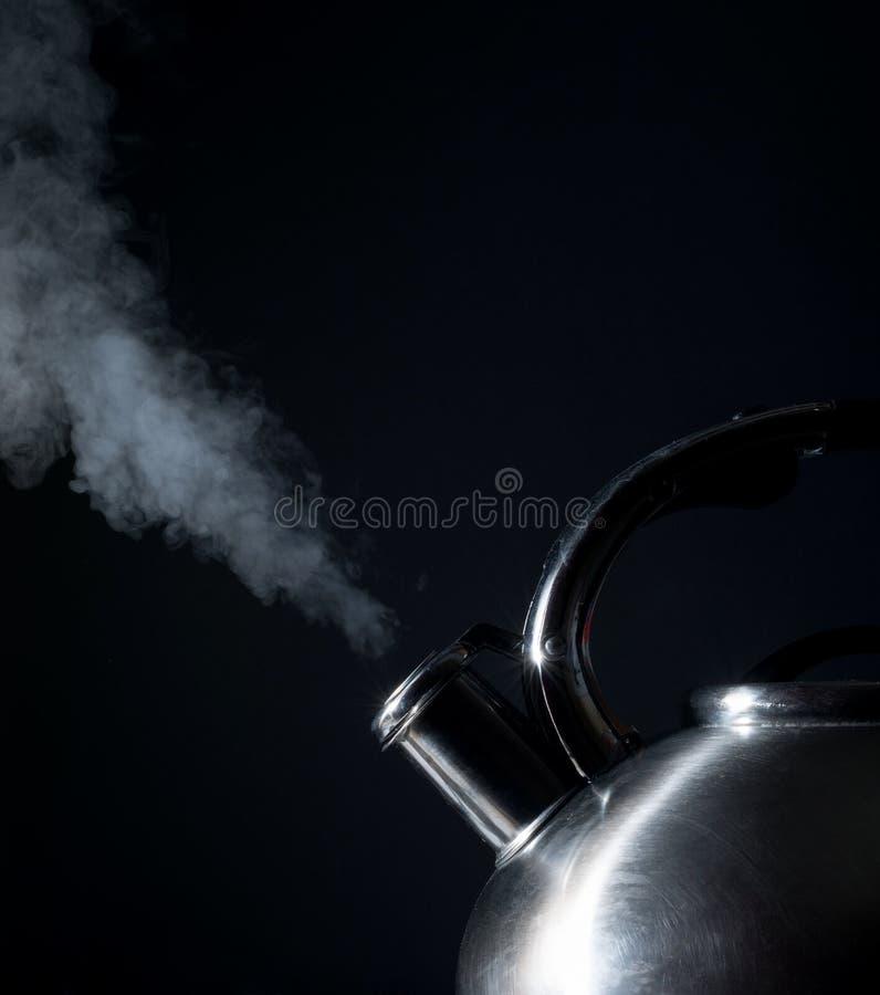 Bouilloire sifflant, bouilloire de ébullition, vapeur, sur un noir photographie stock libre de droits