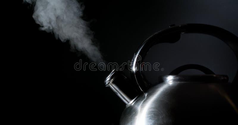 Bouilloire sifflant, bouilloire de ébullition, vapeur, sur un noir image libre de droits