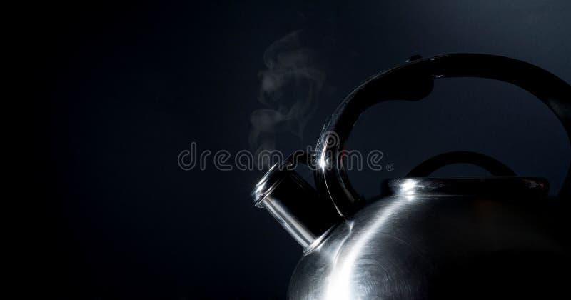 Bouilloire sifflant, bouilloire de ébullition, vapeur, sur un noir images stock