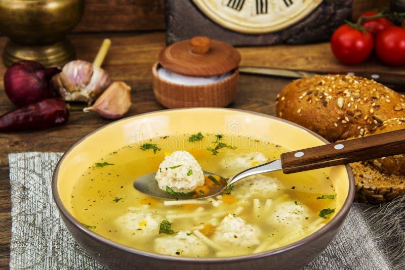 Bouillon avec des boulettes de viande et des nouilles de poulet dans la cuvette en céramique photo stock