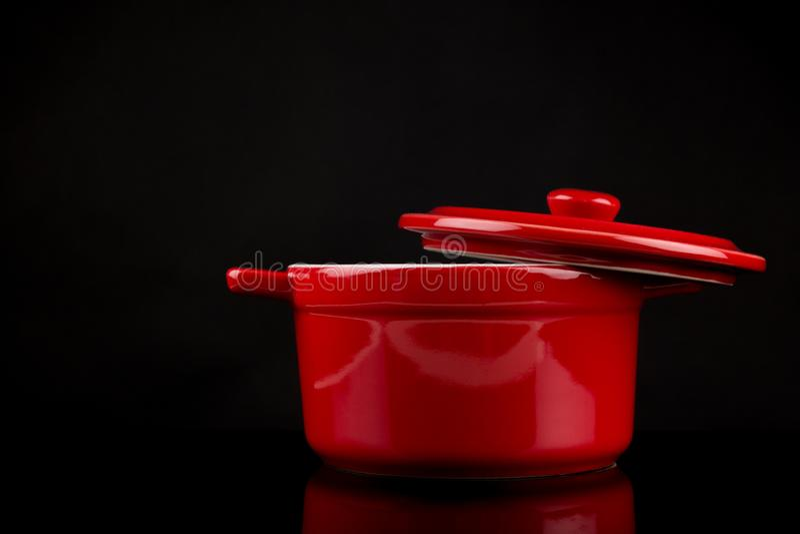 Bouillonketel, Rode bouillonketel met open die slot aan de kant op zwarte achtergrond met bezinningen wordt geïsoleerd, exemplaar stock fotografie