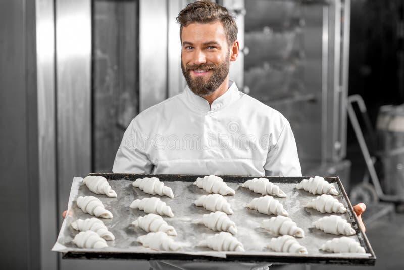 Boulanger beau jugeant le plateau plein des croisants fraîchement cuits au four image stock