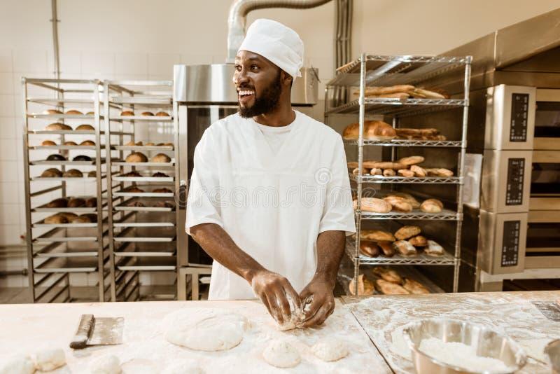 boulanger d'afro-américain préparant la pâte crue pour la pâtisserie images stock