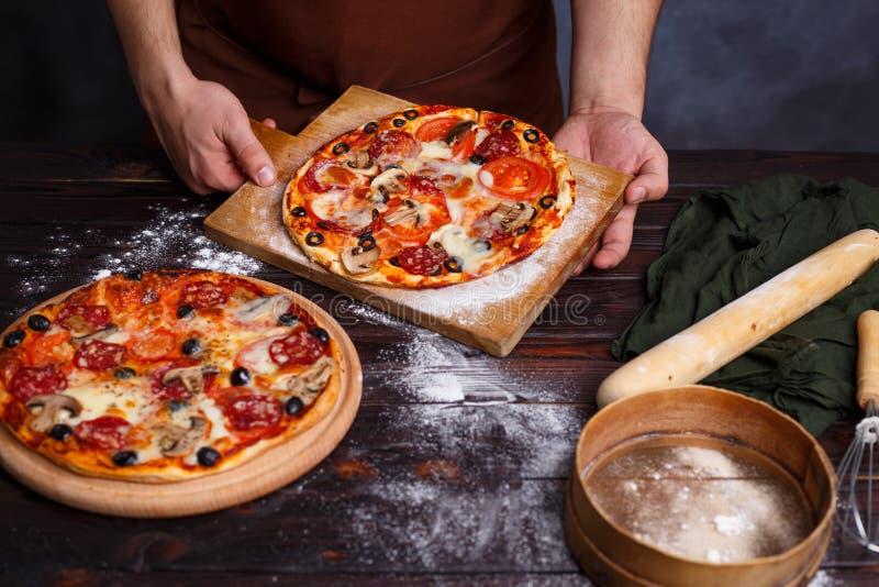 Boulanger de chef avec la pizza fraîchement cuite au four Procédé de cuisson, FO italiennes images stock