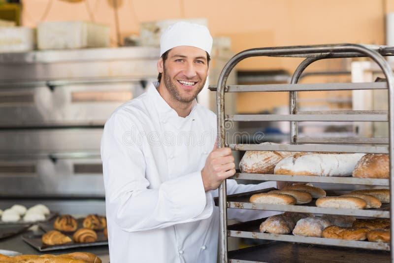 Boulanger de sourire poussant le plateau du pain images stock
