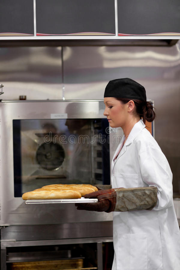 Boulanger féminin sérieux avec des baguettes photo libre de droits
