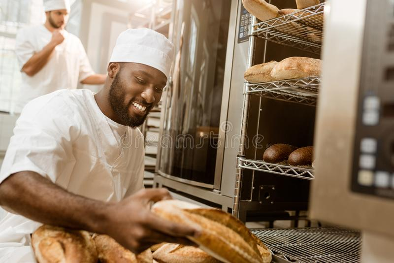 boulanger heureux d'afro-américain avec le plateau des miches de pain fraîches photos stock