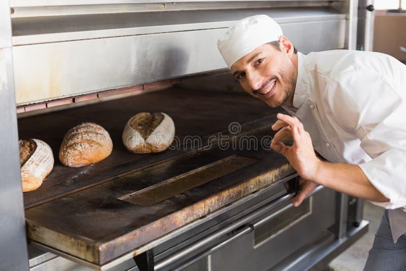 Boulanger heureux par le four ouvert photos stock