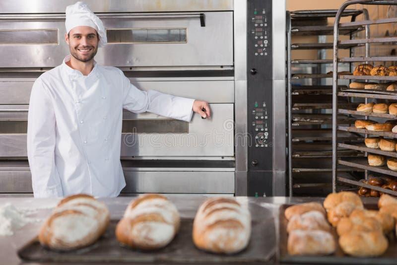 Boulanger heureux se penchant sur le four professionnel image stock