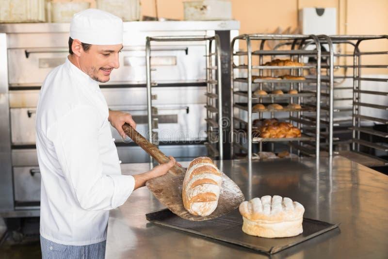 Boulanger heureux sortant le pain frais photo libre de droits