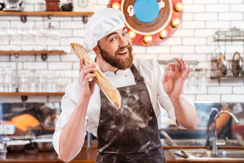 Boulanger heureux tenant la miche de pain et montrant le signe correct images stock